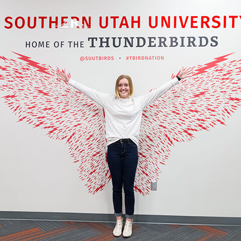 A student in front of wings painted on a wall.
